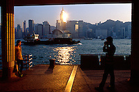 A man photographs a woman at the Promenade at sunset, overlooking Victoria Harbour and the city skyline, Kowloon, Hong Kong, China.