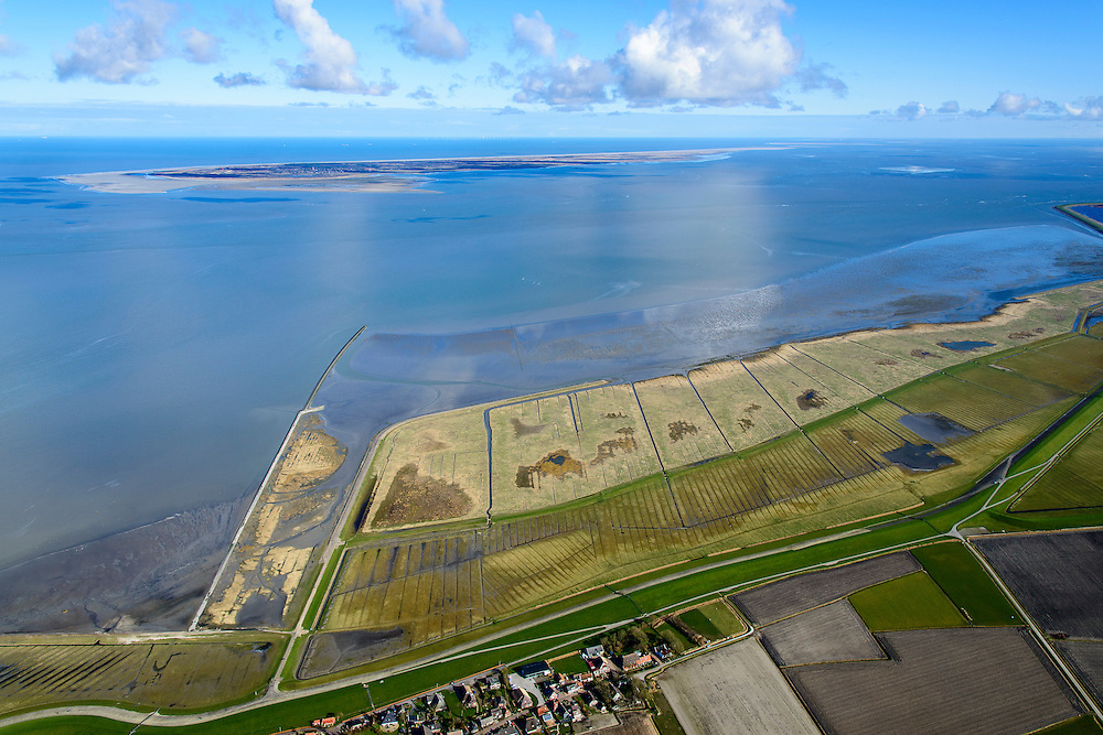 Nederland, Friesland, Gemeente Dongeradeel, 28-02-2016; Paesens-Moddergat met Peazemerlannen, buitendijkse zomerpolder, nu kweldergebied grenzend aan het Wierumerwad en de Waddenzeee. Het gebied is ontstaan door spontane uitpoldering bij storm in 1973 waarbij er een gat geslagen werd in de dijk. Het natuurgebied is in beheer bij It Fryske Gea. Aan de horizon de Schiermonnikoog.<br /> <br /> The village Paesens and Peazemerlannen, salt marshes bordering the Wierumerwad and Waddenzeee. The area has been created in 1973, a severe storm made a hole in the outside polder dike. Below the seawall (delta height), in the middle the dike of the summer polder.<br /> <br /> luchtfoto (toeslag op standard tarieven);<br /> aerial photo (additional fee required);<br /> copyright foto/photo Siebe Swart
