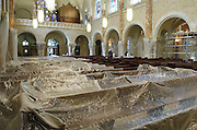 Newly refinished pews are covered with sheets of plastic during the finishing stages of renovation at the National Shrine of Mary, Help of Christians. The plastic was removed March 24 as the shrine hosts its first liturgy on Holy Thursday, the Mass of the Lord's Supper. (Catholic Herald photo by Sam Lucero)