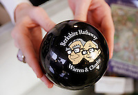 """A clerk holds a """"magic answer ball"""" featuring images of Berkshire Hathaway Chairman Warren Buffett (L) and Vice-Chairman Charlie Munger at the company's annual meeting weekend in Omaha, Nebraska May 1, 2011.  .REUTERS/Rick Wilking  (UNITED STATES)"""