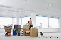 Office worker standing holding potted plant near cartons and equipment on floor of empty office space