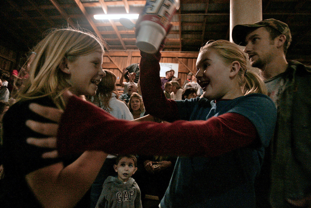 Jessica Edwards, 10, Amber Huber, 10, greet each other at the Tri-County Cowboy Church held inside the Circle K horse arena in Mount Pleasant.