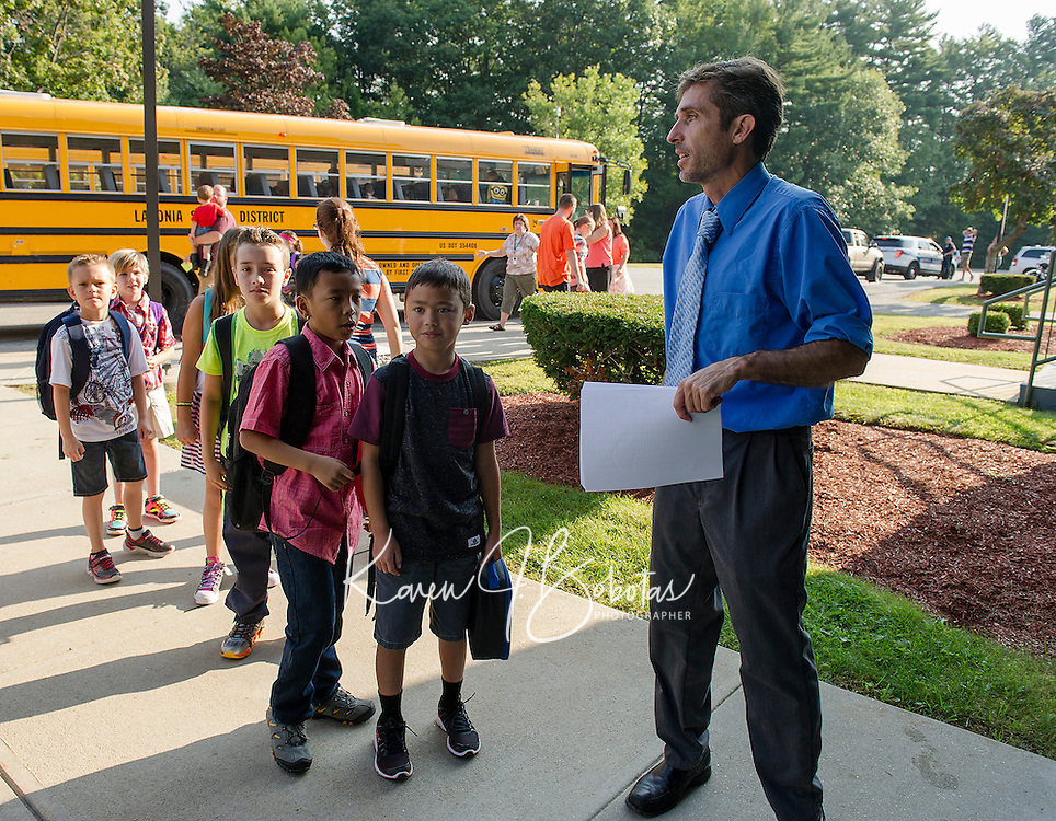 Mr. Beyer welcomes students into Woodland Heights Elementary School for their first day of classes on Monday morning.  (Karen Bobotas/for the Laconia Daily Sun)