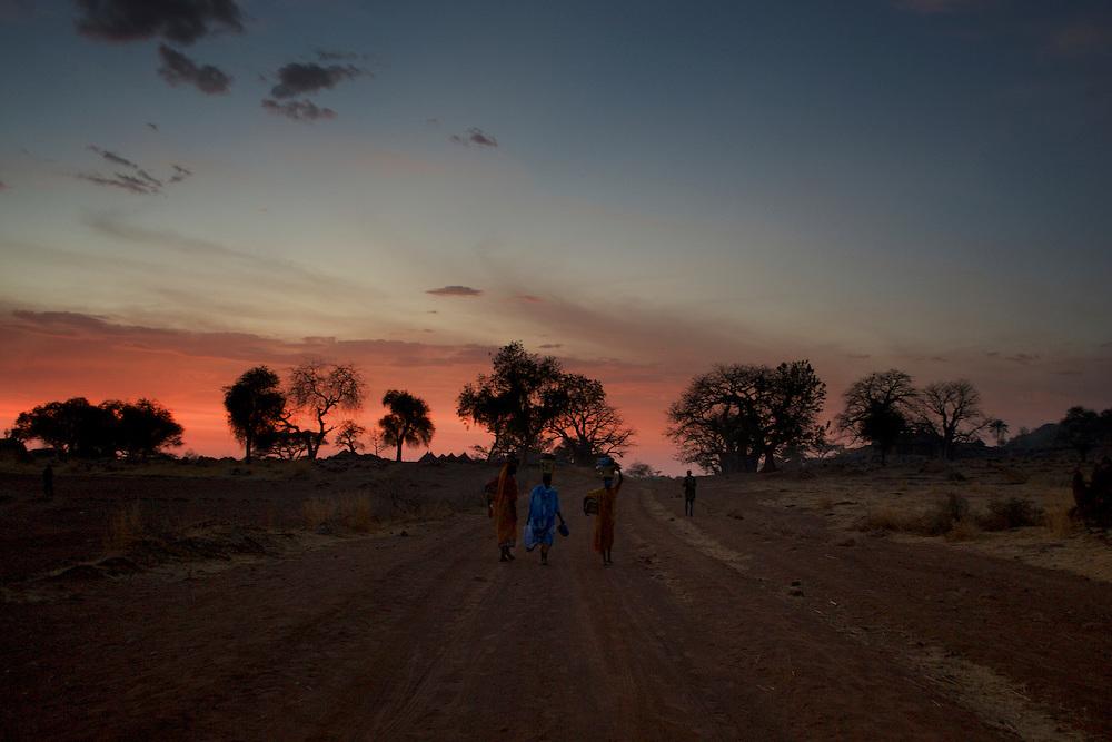 Local women walk along a road near the Nuba village of Tess in South Kordofan.