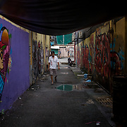 A man walks in back lane of Jalan Petaling and Jalan Panggong in Kuala Lumpur which both sides of wall painted with graffiti on November 8, 2017.
