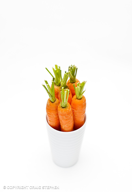 Selection of babay carrots in a white jar against a white background