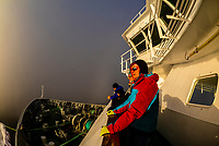 Passengers stand on deck while the Hurtigruten ship Nordlys is docked in port at Finnsnes, surrounded by sea fog, Arctic, Northern Norway.