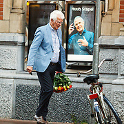 NLD/Amsterdam/20150529 - Gerard Cox loopt door Amsterdam in de regen met een bos bloemen