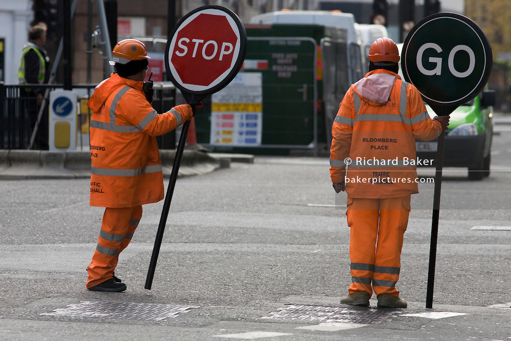 Construction site traffic marshals show conflicting information to oncoming traffic in the City of London.