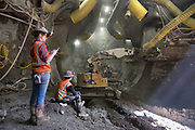 A geotechnical inspector checks readings while a large excavator chips away at reinforced shotcrete to begin the next phase of excavation for the platform cavern.