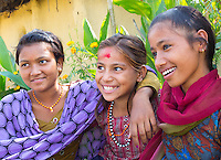 Three happy young Nepalese girls smiling in a rural Terai village, Nepal