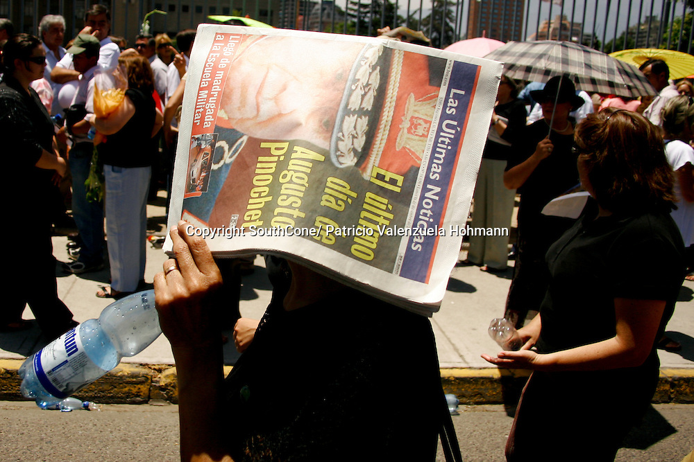 A supporter protects from sun with local newspaper.<br /> December 2006, The Chilean Dictator Augusto Pinochet died in Santiago Chile. As news spread thousands went out the streets either to celebrate o mourn Pinochet who lead the 1973 coup that overthrew the democratically elected president Salvador Allende. Pinochet's 17 year regime killed and disappeared around 4.000 people, tortured and exile around 20.000. On 1989 he lost elections and democracy was regained. He died on late December 2006. December 2006, The Chilean Dictator Augusto Pinochet died in Santiago Chile. As news spread thousands went out the streets either to celebrate o mourn Pinochet who lead the 1973 coup that overthrew the democratically elected president Salvador Allende. Pinochet's 17 year December 2006, The Chilean Dictator Augusto Pinochet died in Santiago Chile. As news spread thousands went out the streets either to celebrate o mourn Pinochet who lead the 1973 coup that overthrew the democratically elected president Salvador Allende. Pinochet's 17 year.