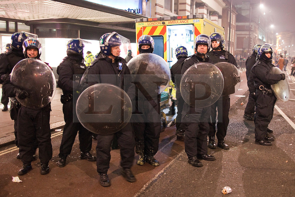 "© under license to London News Pictures. 25/03/2011: Police protect a fellow officer who lies injured on the ground, as paramedics attend to him. He was later taken aboard an ambulance. The officer was injured during large anticuts protests in Central London. Credit should read ""Joel Goodman/London News Pictures""."