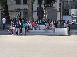 © Licensed to London News Pictures. 06/08/2018. London, UK.  Tourists shelter in the shade form the sun, next to a statue of Gandhi on Parliament Square as hot weather continues in the capital. Photo credit: Ben Cawthra/LNP