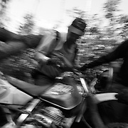 Digby, Nol and Billy carry a bike under a fallen tree blocking their path on the Ho Chi Minh Trail in Laos. ....