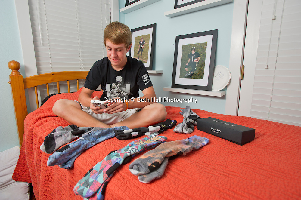 """Winston Robson, 15, of Bentonville, Ark., texts while sitting with his sock collection made by Rock """"Em Apparel in his room Tuesday, Sept. 10, 2013, in Bentonville, Ark. Robson owns several pair of the custom Nike Elite socks. Photo by Beth Hall"""