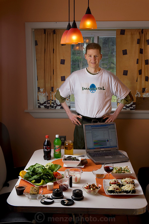 "Michael Rae, with his typical day's worth of precisely weighed food that comprises his calorie restricted daily diet, in the kitchen of his suburban Philadelphia home. (From the book What I Eat: Around the World in 80 Diets.) The caloric value of his day's worth of food in July was fixed at 1,900 kcals. He is 32; 5'11,5"" and 114 pounds. Michael is research assistant to the theoretician and biomedical gerontologist Aubrey de Grey, and they are the coauthors of the book ""Ending Aging""."