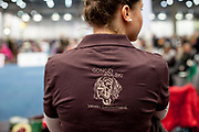 Woman wearing a shirt of the German society of Polish Hunting Dogs  during the ring competition at the Leipzig Trade Fair. Over 31,000 dogs from 73 nations will come together from 8-12 November 2017 in Leipzig for the biggest dog show in the world.