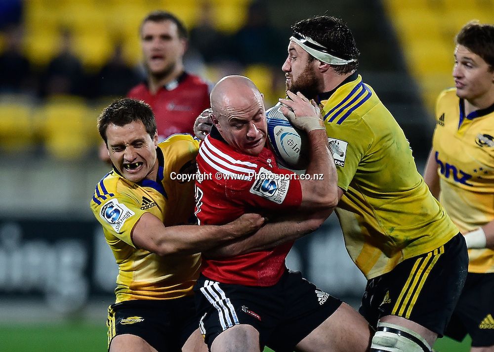 Willi Heinz of the Crusaders is tackled by Tim Bateman and Jeremy Thrush, captain of the Hurricanes during the Super Rugby - Hurricanes v  Crusaders rugby match at the Westpac Stadium in Wellington, New Zealand on the 28th of June 2014. Photo: Marty Melville/www.Photosport.co.nz