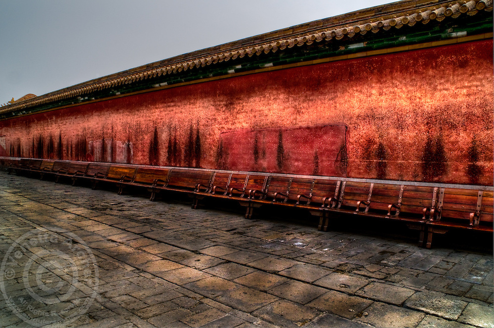 A row of wooden benches line a wall within the Forbidden City.