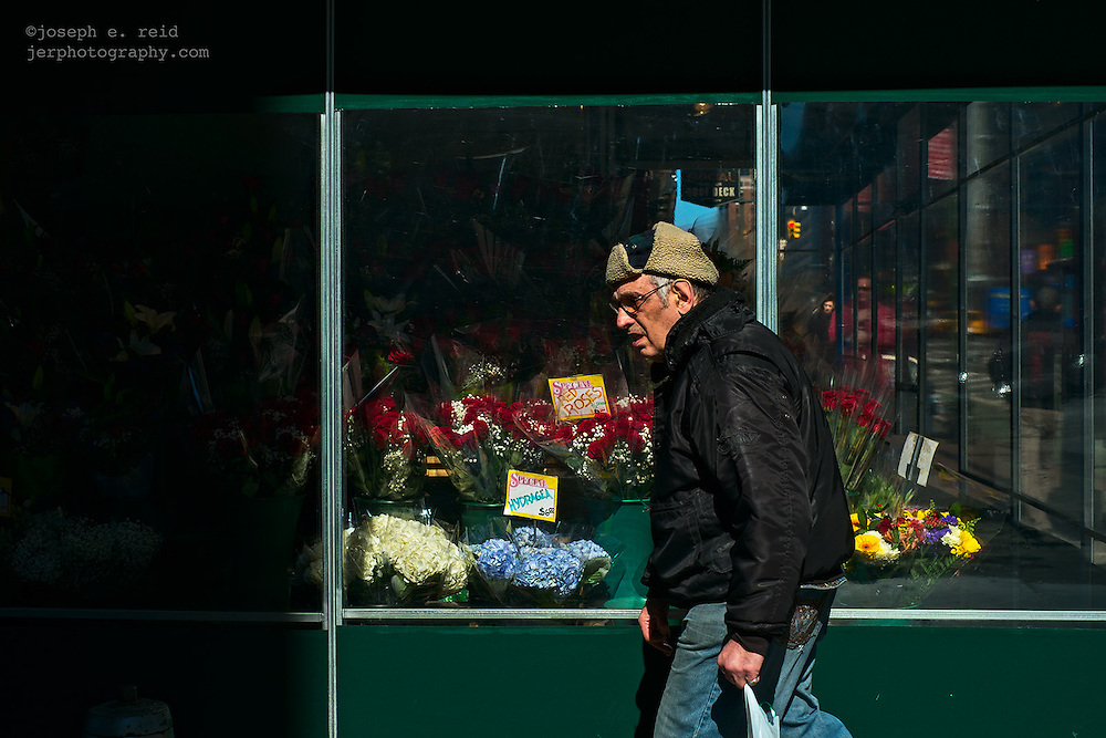 Man passing shop selling flowers