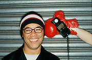 A hand in a boxing glove holding a light meter up to a smiling DJ Ashley Beedle in a beanie hat