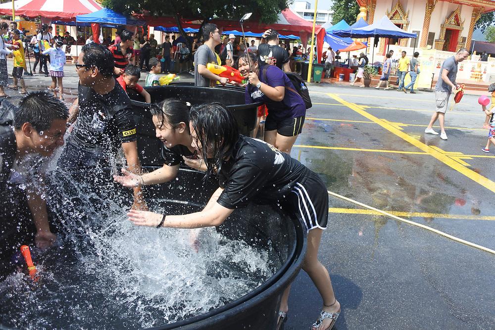 Two Girls  splashing a man at the Songkran water festical in Penang