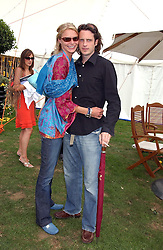 Model JODIE KIDD and MR AIDEN BUTLER at the 2004 Cartier International polo day at Guards Polo Club, Windsor Great Park, Berkshire on 25th July 2004.