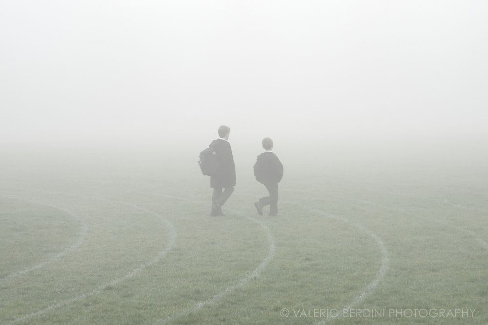 Two students walking through the fog on the large green in Parker's Piece in Cambridge, England.