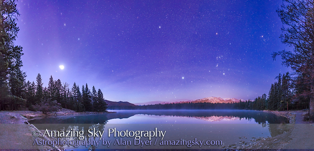 A panorama of roughly 120&deg; showing a star- and planet-filled sky in the dawn twilight over Lake Annette in Jasper National Park, Alberta, on the morning of October 25, 2015. <br /> <br /> At left, to the east, are the two bright planets, Venus (brightest) and Jupiter in a close conjunction 1&deg; apart (and here almost merging into one glow), plus reddish Mars below them, all in Leo, with the bright star Regulus above them. Right of centre, to the south, is Orion and Canis Major, with the bright star Sirius low in the south. At upper right are the stars of Taurus, including Aldebaran and the Hyades star cluster. Venus was near greatest elongation on this morning. <br /> <br /> No special filter was employed here &mdash; the hazy planets and stars and colourful star images comes naturally from a high haze over the sky this morning. It bloats the images of Venus and Jupiter so they almost merge. <br /> <br /> The stars are partly reflected in the waters, with rising mist in the distance on the lake.<br /> <br /> Distant Whistler peak below Orion is lit by lights from the Jasper Townsite. The site is the shore of Lake Annette near the Jasper Park Lodge and site of the annual star party held as part of the Jasper Dark Sky Festival. I shot this scene the morning after the 2015 Festival.<br /> <br /> This is a panorama of 8 segments, shot with the 24mm lens mounted vertically (portrait), each for 25 seconds at f/2.8 with the Canon 6D at ISO 3200. Stitched with Photoshop, with some vertical scaling to reduce the distortion introduced by the pan mapping process.