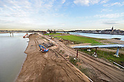 Nederland, Nijmegen, 23-11-2015 De 4km. lange nevengeul aan de overkant van de Waal bij Lent nadert zijn voltooiing. Laatste werkzaamheden. Grootste onderdeel van de vele werken van Rijkswaterstaat om bij hoogwater een betere waterafvoer in de rivier te hebben. In precies drie jaar is het werk uitgevoerd. Het is een omvangrijk project waarbij onder meer de pijlers van het spoorviaduct een bredere basis kregen omdat die straks in de loop van het water staan. Ook de n325 die vanaf de Waalbrug naar Arnhem loopt is over 400 meter opnieuw aangelegd omdat het talud vervangen wordt door een nieuwe brug met drie gracieuze pijlers. Het dorp veurlent komt op een kunstmatig eiland te liggen met twee bruggen als ontsluiting. Een voetgangersbrug en een andere, de Promenadebrug, voor normaal verkeer. Inmiddels begint de nieuwe kade aan de noordkant van deze geul vorm te krijgen. Ruimte voor de rivier, water, waal. In de nieuwe dijk is een drempel gebouwd die stapsgewijs water doorlaat en bij hoogwater overloopt. The Netherlands, Nijmegen Measures taken by Nijmegen to give the river Waal, Rhine, more space to flow during highwater and to prevent the risk of flooding. Room for the river. Reducing the level, waterlevel. Large project to create a new paralel gully, an extra flow of water, so the river can drain more water during highwater. Due to climate change and expected rise, increase of the sealevel, the Dutch continue to protect their land from the water. Foto: Flip Franssen
