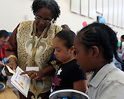 "Sandra Fink, left, a retired Rochester City School District science teacher, helps Jaelyn Jackson, 8, center, and Lamar Scott, 8, read their certificates of completion at a celebration of the ""Help Me Read"" program at Enrico Fermi Elementary School No. 17 in Rochester on Monday, June 2, 2014. The tutoring program helped 137 children improve their reading ability, with some students making jumps of several grade levels in one year."