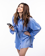 Pretty young  Hispanic woman in men's dress shirt holding a cell phone
