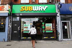 © Licensed to London News Pictures. 22/05/2020. London, UK. A woman waits outside Subway, a fast food restaurant in Wood Green, north London as lockdown restrictions are eased. Photo credit: Dinendra Haria/LNP