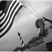 Roland Whitted, a seasonal Park Ranger at Cape Hatteras Light Station on the Cape Hatteras National Seashore, raises an American flag before the park opens.<br /> Whitted, originally from Marquette, Michigan, cites learning as his motivation for work. ?I enjoy coming to a new place and learning things I didn't know.? Though Whitted hails from a state with 116 lighthouses he admits, ?I knew nothing about lighthouses until I came to work here.? <br /> (Jason A. Frizzelle)