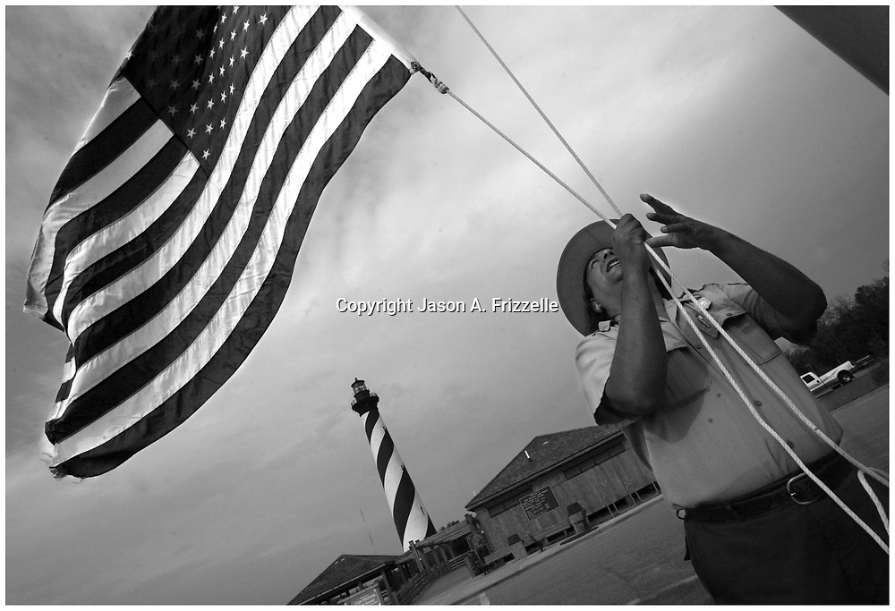Roland Whitted, a seasonal Park Ranger at Cape Hatteras Light Station on the Cape Hatteras National Seashore, raises an American flag before the park opens.	<br /> 	Whitted, originally from Marquette, Michigan, cites learning as his motivation for work. ?I enjoy coming to a new place and learning things I didn't know.? Though Whitted hails from a state with 116 lighthouses he admits, ?I knew nothing about lighthouses until I came to work here.? <br /> (Jason A. Frizzelle)