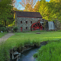 The Wayside Inn Grist Mill in Sudbury Massachusetts on a beautiful spring morning. I am glad I hung around a bit since the sky finally broke open and the scenery became alive. The warm morning sunlight painted the tree canopies in beautiful spring colors which stand in nice contrast with the darker foreground of the historic landmark. A long exposure setting conveys the flowing water of the brook in front of the view and across the waterfall at the Grist Mill.<br />