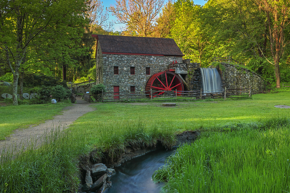 The Wayside Inn Grist Mill in Sudbury Massachusetts on a beautiful spring morning. I am glad I hung around a bit since the sky finally broke open and the scenery became alive. The warm morning sunlight painted the tree canopies in beautiful spring colors which stand in nice contrast with the darker foreground of the historic landmark. A long exposure setting conveys the flowing water of the brook in front of the view and across the waterfall at the Grist Mill.<br /> <br /> Sudbury Grist Mill photography images are available as museum quality photo, canvas, acrylic, wood or metal prints. Wall art prints may be framed and matted to the individual liking and interior design decoration needs:<br /> <br /> https://juergen-roth.pixels.com/featured/wayside-inn-grist-mill-juergen-roth.html<br /> <br /> Good light and happy photo making!<br /> <br /> My best,<br /> <br /> Juergen<br /> Licensing: http://www.rothgalleries.com<br /> Photo Prints: http://fineartamerica.com/profiles/juergen-roth.html<br /> Photo Blog: http://whereintheworldisjuergen.blogspot.com<br /> Instagram: https://www.instagram.com/rothgalleries<br /> Twitter: https://twitter.com/naturefineart<br /> Facebook: https://www.facebook.com/naturefineart