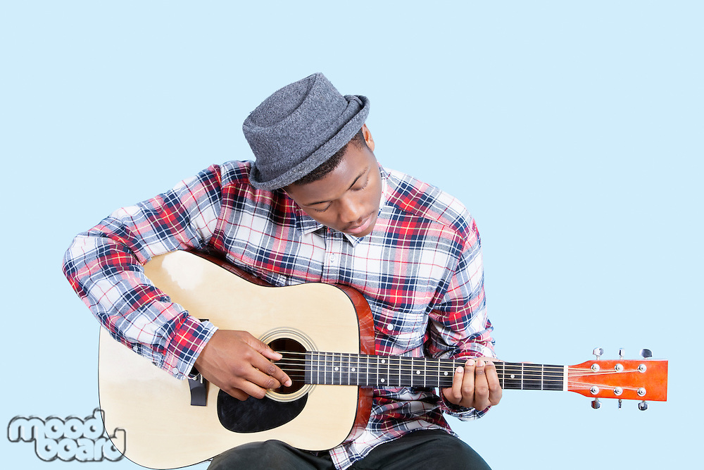 Young man wearing hat as he plays guitar over light blue background