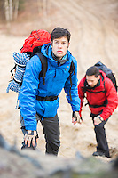 Young male backpackers hiking in forest