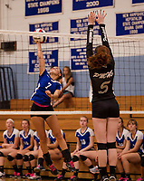 Interlakes Morgan White goes up for a spike with Prospect Mountain's Hannah Bureau blocking at the net during NHIAA Division III volleyball Monday evening.  (Karen Bobotas/for the Laconia Daily Sun)