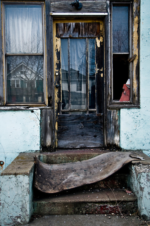"""The doorway of an abandoned home where blocks of abandoned homes and small signs of life are all that remain in certain areas of Gary, IN. Gary is part of America's Midwestern """"Rust Belt"""", the heartland of the country and home to big unionized manufacturers like the auto and steel industries."""