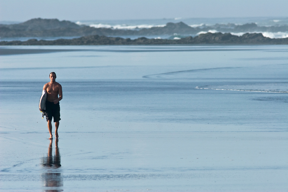 A surfer walks along the beach after an early morning surf session in Marbella Costa Rica. He is carrying his surfboard