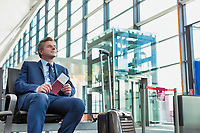 Portrait of Mature businessman sitting and holding his passport while waiting in gate for boarding at airport