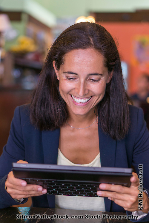 Stock Photo of Woman in Cafe using Tablet Computer (Model Released)