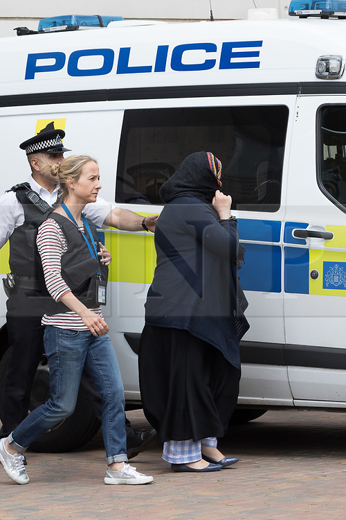 © Licensed to London News Pictures. 04/06/2017. LONDON, UK.  A covered women is removed by police officers outside the block of flats in Kings Road, Barking that police raided this today in connection with terror attack and four women were removed from the flats by police this lunchtime.  Photo credit: Vickie Flores/LNP