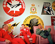 Flight Lieutenants Steve Underwood and Anthony Parkinson and Wing Commander Bill Ramsey of the elite 'Red Arrows', Britain's prestigious Royal Air Force aerobatic team, discuss logistics beneath the emblems of long-disbanded fighter squadrons which decorate the squadron building at RAF Akrotiri, Cyprus. They sit in faded pink armchairs supplied by the Ministry of Defence (MoD) that are seen in many RAF stations and airfields with the same drab blue paint on the walls. Painted by hand are circular badges  with bold colours (colors) and illustrations of birds of prey, fighter-jets, swords and shields which all symbolise  warfare. The three pilots are relaxed wearing their red flying suits with their sunglasses dangling in the regulation loop, they are holding a bottle of mineral water and a coffee cup.