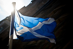 Scottish Saltire and the Lion Rampant flags in the sunlight in Edinburgh.