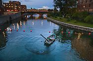 Båt fiskar med håv i Stockholms ström utanför Riksdagshuset i Stockholm