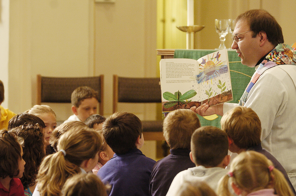 Fr. Mark Danczyk reads a book to students at St. Louis Catholic Academy in Caledonia, Wis. during his homily at a school Mass. A dwindling enrollment forced the Catholic school to close its doors in 2005. (Photo by Sam Lucero)